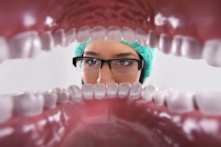 Female dentist over open patients mouth looking in teeth photo