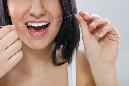 dental floss:  Close-up of a woman flossing his teeth with dental floss Stock Photo