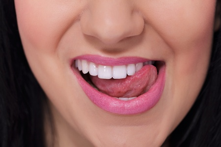 Close-up of a female mouth and white teeth which she touches with her tongue Stock Photo - 12924409