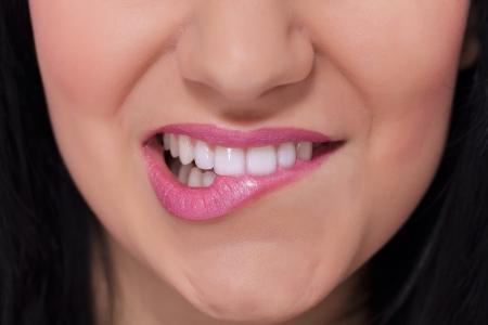 Close-up of a female lips biting  white teeth  photo