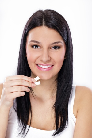 chewing gum:  young woman holding chewing gums in her hand.