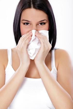 tosiendo: Primer plano de una mujer joven estornudar en un pañuelo