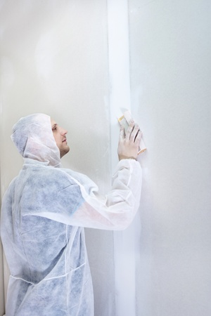 Plasterer finishing his work, working with sandpaper photo