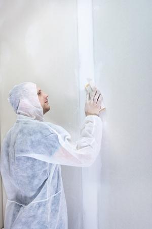 sandpaper: Plasterer finishing his work, working with sandpaper
