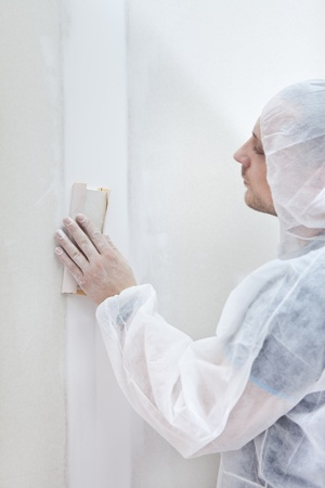 Apartment repair, processing of a wall by an sandpaper photo