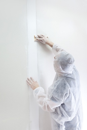 Plasterer at work doing indoor house repair with plaster photo