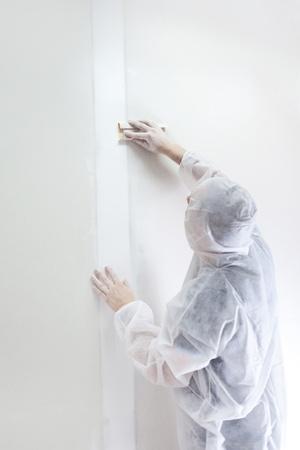 sandpaper:  Plasterer at work doing indoor house repair with plaster