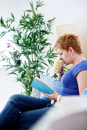 Portrait of beautiful woman sitting on sofa drinking coffee and reading book, side view Stock Photo - 12938801