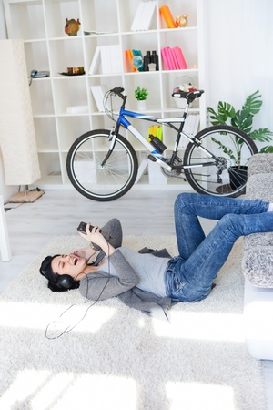 girl lying on floor in living room and listening music through smart phone Stock Photo - 12938877
