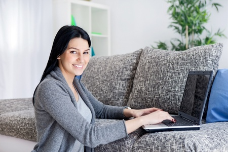 Woman sitting on floor  working with computer at home in  living room. Stock Photo - 12938740