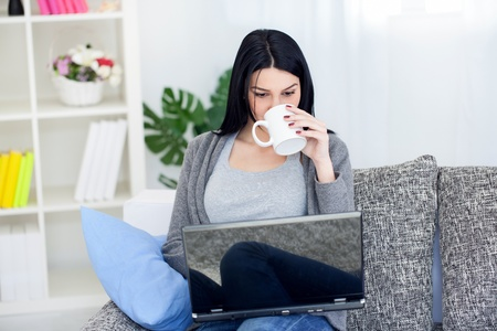 Smiling young woman drinking coffee or tea while using laptop at home Stock Photo - 12938739