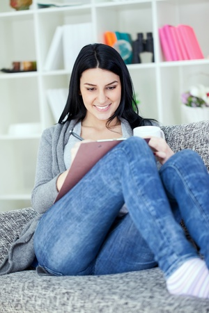Attractive  Woman Writing in a Notebook on Sofa photo