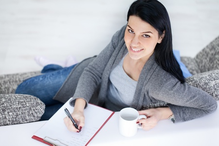 Smiling young girl drinking tea and making note , domestic life, Stock Photo - 12938907