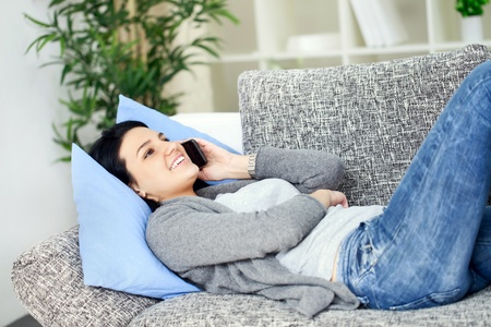 Beautiful happy woman on a sofa making a phone call Stock Photo - 12938754
