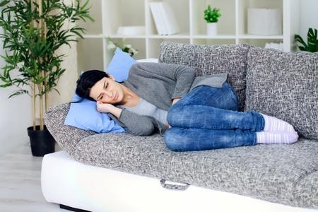 желудок: Молодая женщина, лежа на кровати и имеющие боль в животе
