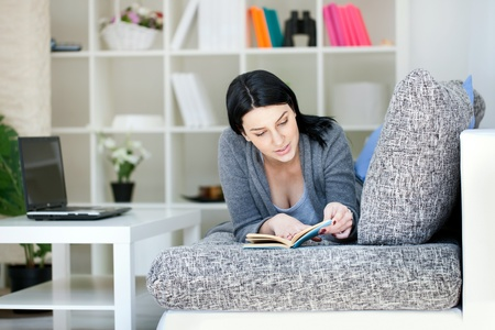 Young woman relaxing with a book while lying on a sofa in her living room Stock Photo - 12938789