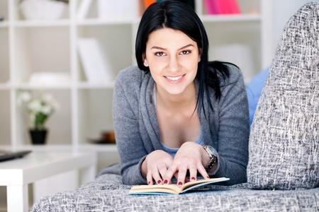 Entspannte Frau liegt auf dem Sofa und genie�en Lesebuch