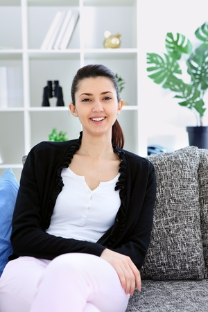 Portrait of young woman sitting on couch at home, looking at camera smiling Stock Photo - 12939201