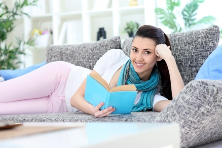 charming woman lying on sofa reading a book looking into camera in living room photo