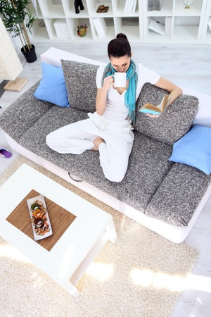 Young woman sitting on couch in living room reading book and drinking tea