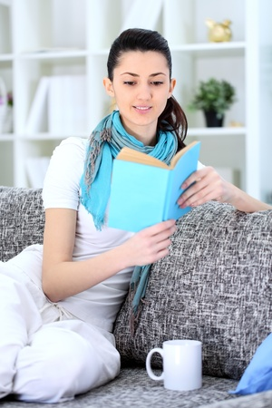 pleasure of reading:  Young woman sitting on sofa and reading book