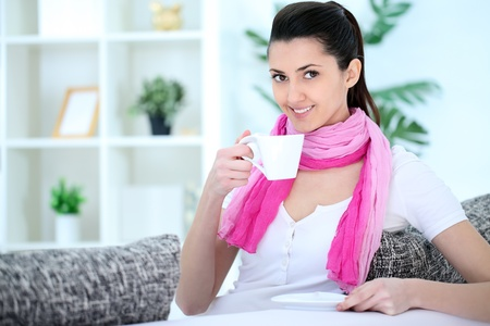 Cheerful young woman sitting on sofa and drinking  coffee  photo