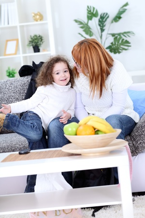 tickling:  Mother with her little daughter in living room Stock Photo