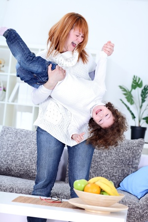 tickling: Mother playing with her daughter  at home
