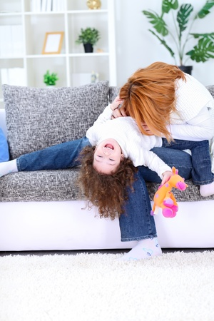 tickling: Cheerful young mother playing with her daughter on couch at home