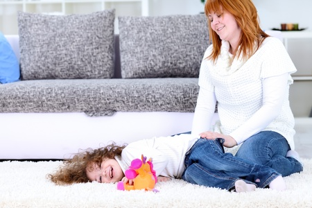 tickling:  mother with her happy  daughter, playing on floor at home