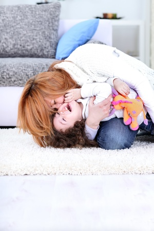 tickling: Mom tickles her child, playing and laughing