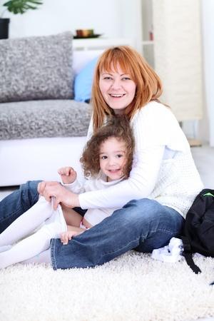 niños vistiendose: los pantalones vaqueros de fijación de la madre de su hija