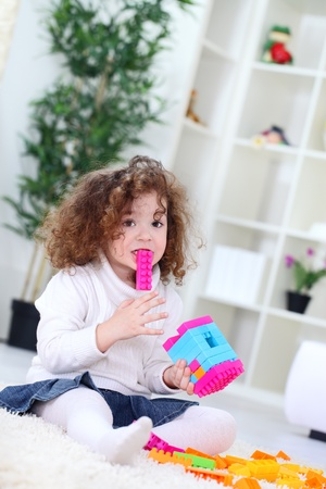 funny little girl playing with construction blocks, holding block in mouth  photo