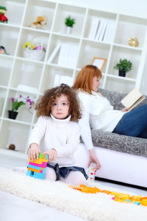 Cute girl playing with  cubes blocks , mother on sofa reading book  photo