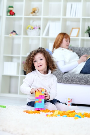 Little girl playing on floor in living room with mother in background , domestic life photo