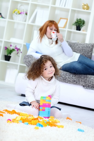 Sweet girl playing with her toys, her mother relaxing in background  photo