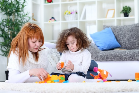mother and baby  girl playing with blocks on living room floor photo