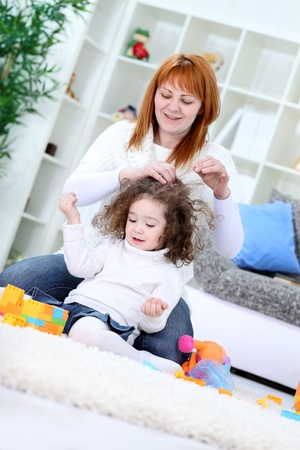 haciendo el amor: Madre sentada en el suelo y cepillarse el cabello de su hija Foto de archivo