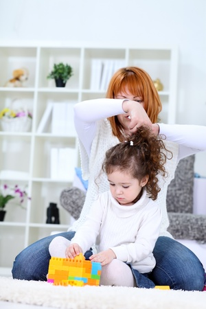 Mother  fixing daughters hair at home photo