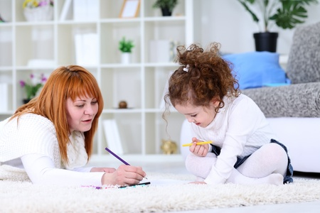 Young mom and her little daughter painting together, playful photo