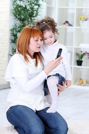 Mother and child using a mobile phone together photo