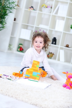 Little girl playing with her toys on floor  photo