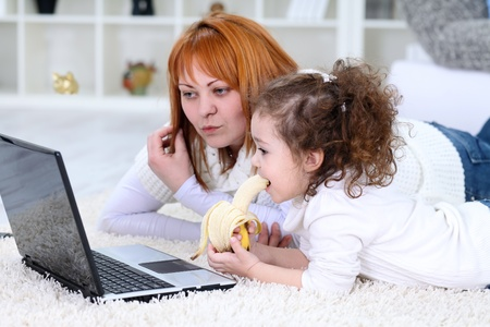 eating banana:  Little girl and mother with laptop at home
