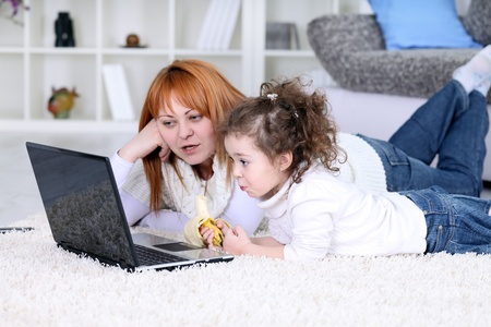 mother and daughter looking  cartoon on laptop photo
