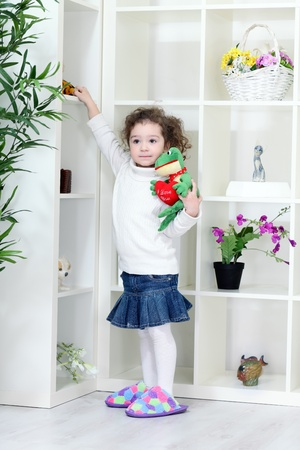Little girl taking all toys from the shelves, tyke photo