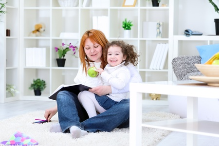 Smiling girl sitting in the lap of her mother photo