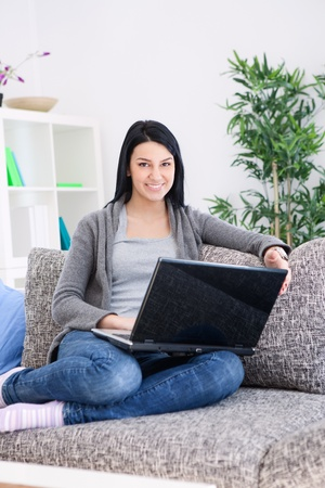relaxing woman in living room sitting on sofa using laptop  photo