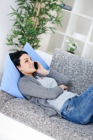 Cute teenager girl lying on sofa and  making a phone call Stock Photo - 13092996
