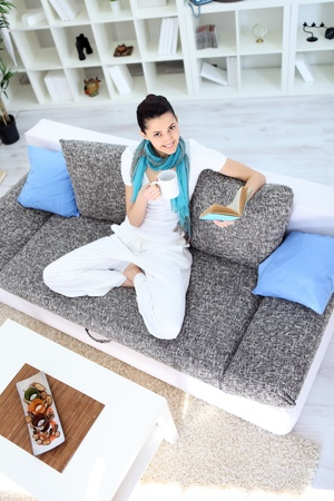 Pretty young woman relaxing on sofa at home and reading book and drinking tea Stock Photo - 13092974