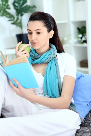 mujer leyendo libro: Chica en el libro de sof� comiendo la manzana y la lectura en casa